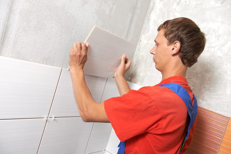 Укладка первого ряда плитки на стену
