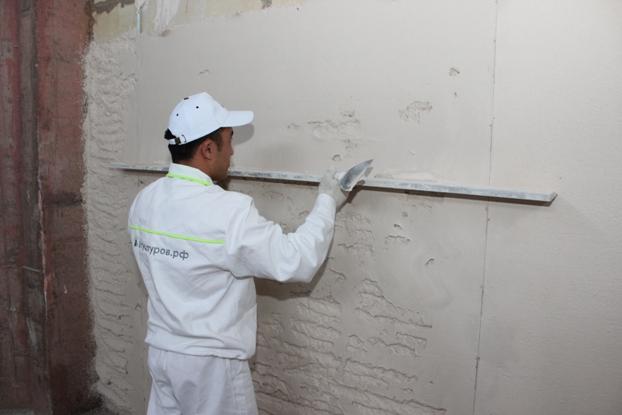 Оштукатуривание стены с маяками